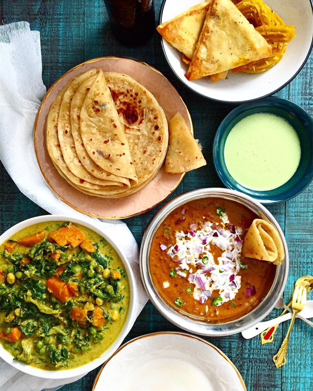 I love dinners like these. A shot from the other day. Spinach, sweet potato and peas in coconut milk, daal makhani, samosas, Indian churros, lime and coriander sour cream chutney and a mega stack of soft chapattis.  #food52 #indianfood #indian #vegetarian #spinach #daal #chapattis #daalmakhani #sweetpotato #rotli #samosas #feast #indianfoodbloggers #ericksonwoodworks #antiqueturquoise #green #indian #instafood #huffposttaste #feedfeed #curry #tastespotting